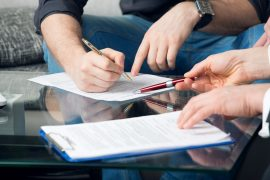 two people signing documents